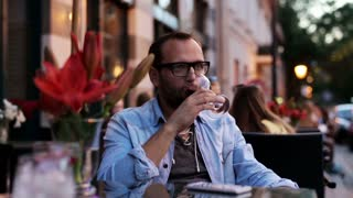 Man drinking wine alone at cafe