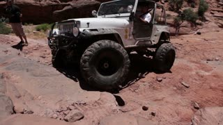 Man driving up rocks in white jeep 1
