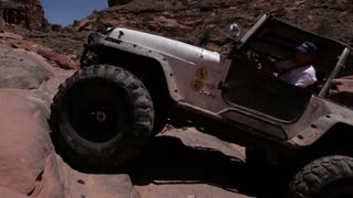 Man driving up rocks in white jeep 2