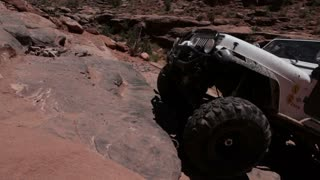 Man driving up rocks in white jeep 3