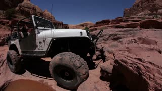 Man driving up rocks in white jeep 4