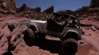 Man driving up rocks in white jeep 5