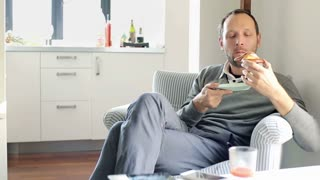 Man eating tasty dessert and drinking juice at home