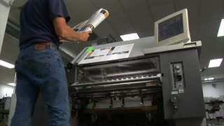 Man Examines Newly Printed Material From Printing Press