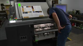 Man Examines Work From Printing Press