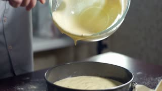 Man extracting liquid cake batter from mixing bowl. Baking cake. Home baking. Baking ingredient. Baking apple pie