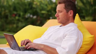 Man finish working on laptop and resting on bed in the evening