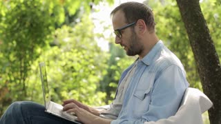 man finishing work on his laptop and relaxing in the garden