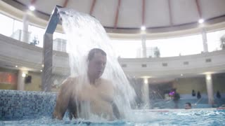 Man getting pleasure under strong water stream in the swimming pool