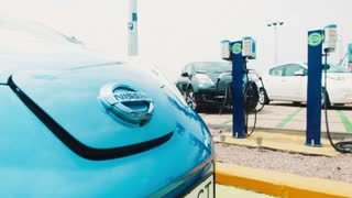 Man getting ready to charge his electric car standing at the charger with his blue car showing the connection point on the bonnet in the foreground