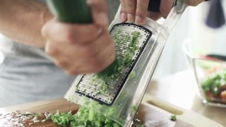Man grating cucumber on grater in kitchen, slow motion shot at 240fps