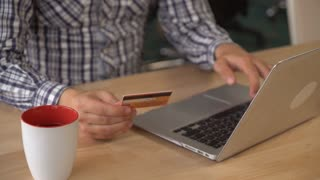 man hands buy online via internet on laptop. Guy sitting at the wooden desk with pc and mug with tea or coffee in the office. Male holding credit card enter security code pay or order some purchase