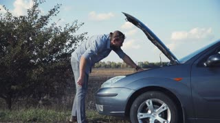 Man in blue jeans having automobile problems and stranded roadside checks under the hood of his car