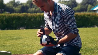 Man in checkered shirt fiddles with appliance while kneeling in large lawn
