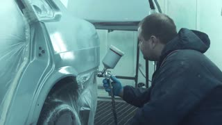 Man in coverall painting car door in white color in paint garage