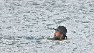 Man in Hat Swimming and Standing in Water