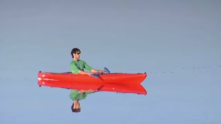 Man In Orange Kayak Paddles On Lake