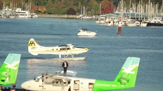 Man in suit walking on plane with plane moving in water in the background