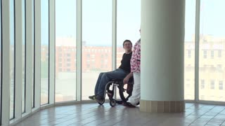 Man in wheelchair talking with nurse in hospital
