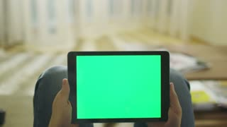 Man is Laying on Couch at Home and Holding Tablet with Green Screen in Landscape Mode on Lap