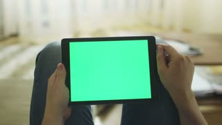 Man is Laying on Couch at Home and Using Tablet with Green Screen in Landscape Mode on Lap
