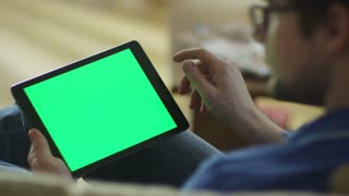 Man is Laying on Couch at Home and Using Tablet with Green Screen in Landscape Mode