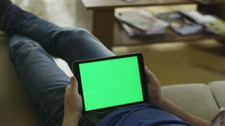 Man is Laying on Couch at Home and Watch on Tablet with Green Screen in Landscape Mode