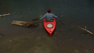 Man Kayaks On Calm Lake In Slow Motion