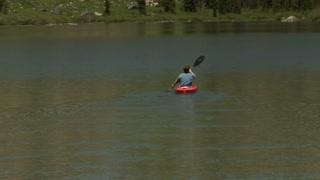 Man Kayaks On Calm Lake