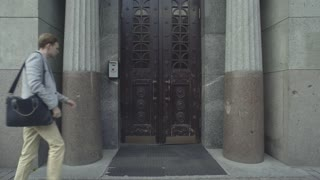 Man looking around and comes at the old door of granite building