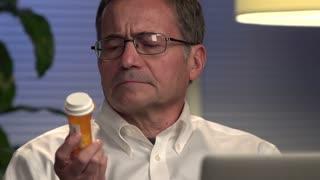 Man looking at prescription at computer - Close