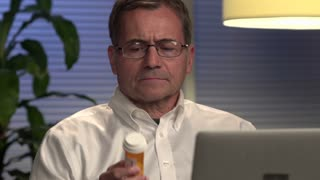 Man looking at prescription at computer