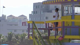Man Looking Over Beach from Lifeguard Tower