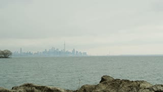 Man Looking Over Lake Ontario to Toronto Skyline