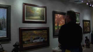 Man Looks At Paintings In Art Gallery