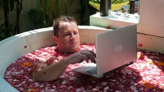 Man lying in the bath and chatting on laptop