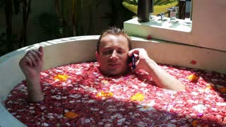 Man lying in the spa with flowers and talking on cellphone