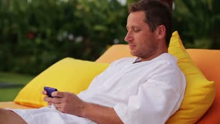 Man lying on bed and texting on cellphone
