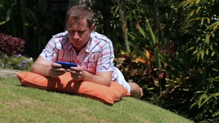 Man lying on grass in the garden and working on cellphone