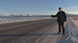 Man on the Side of Alaskan Highway Hitchhiking