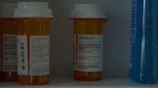 Man opens medicine cabinet, then grabs prescription medicine