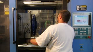 Man Operates Industrial Molding Press