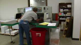 Man Operates Industrial Paper Cutter