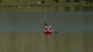 Man Paddles Orange Kayak On Lake Toward Camera