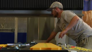 Man Prepares Plastic On Industrial Lathe