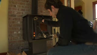 Man Puts Firewood Into Woodstove