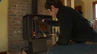 Man Puts Firewood Into Woodstove