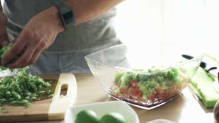 Man putting chopped cucumber into bowl in kitchen, slow motion shot at 240fps