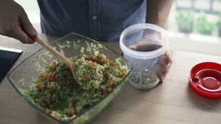 Man putting salad into plastic box in kitchen, slow motion shot at 240fps