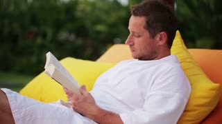 Man reading book and lying on bed